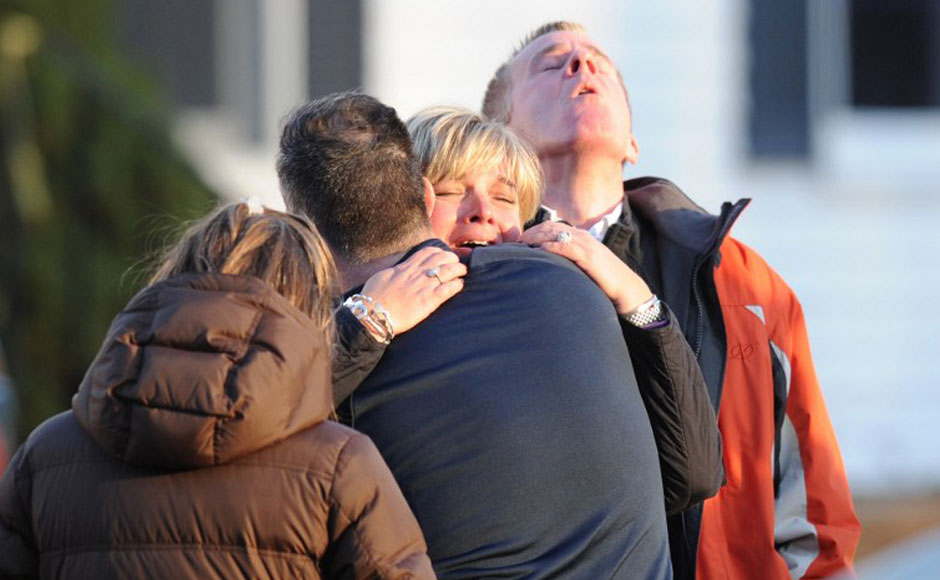 Parents comfort each other after the horrific shootout in the elementary school in Sandy Hook Elementary School in Newtown, Connecticut, northeast of New York City. AFP