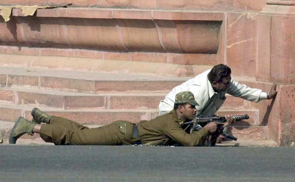 A commando takes-up position besides a plain clothed policeman near Parliament building in New Delhi on 13 December , 2001. A suicide squad stormed India's parliament complex , killing at least six people in an unprecedented attack on the seat of power of the world's biggest democracy. Reuters