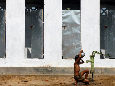 A boy takes bath outside newly built toilets in a village on the outskirts of Nagapattinam, Tamil Nadu. Reuters