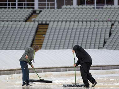 Groundsmen attempt to clear water from the pitch to allow the Australia against New Zealand group stage ICC Trophy cricket match. AP