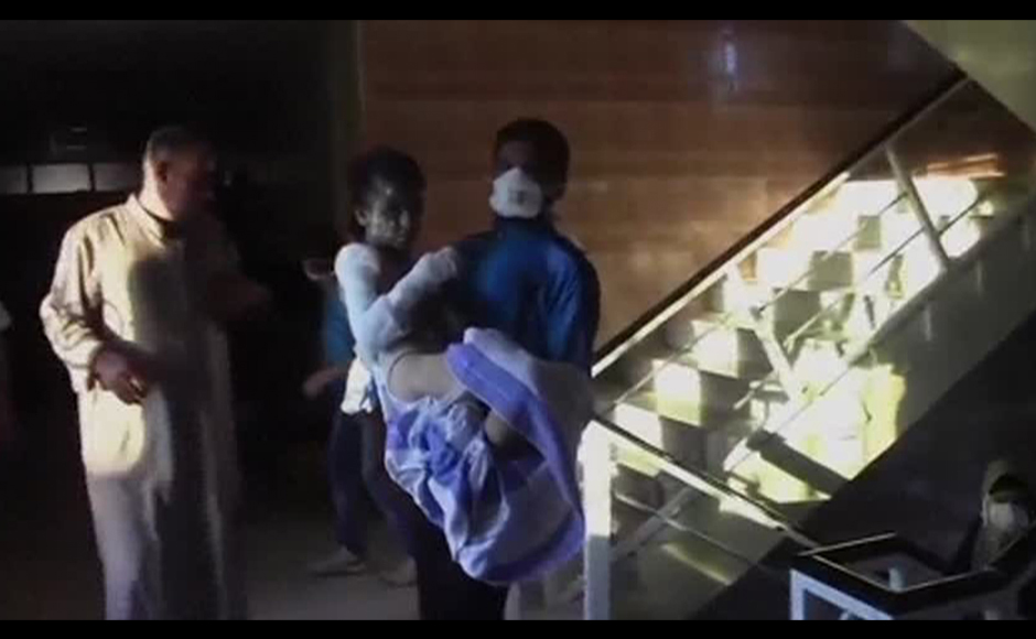 This still image taken from an amateur video off a social media website on August 30, 2013 purportedly shows a man (R) carrying a young woman up a flight of stairs after an attack that according to the video took place on August 26, 2013, at a hospital said to be in the western suburb of Uorm al-Kubra in Aleppo. According to a doctor at the hospital, the chemical attack at an area close to the hospital was similar to napalm, which caused burns on the victims. Reuters
