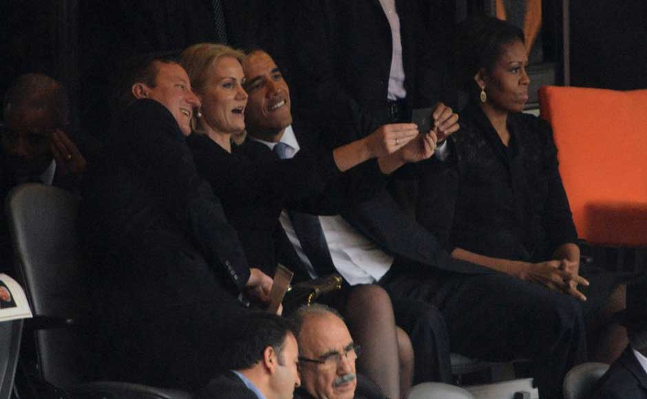 US President Barack Obama and British Prime Minister David Cameron pose for a picture with Denmark's Prime Minister Helle Thorning Schmidt next to US First Lady Michelle Obama during the memorial service of South African former president Nelson Mandela at the FNB Stadium (Soccer City) in Johannesburg. AFP