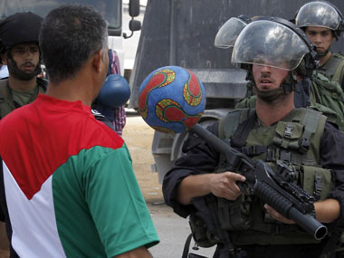 A Palestinian protester juggles a soccer ball in front of Israeli border guards during a demonstration. AFP image