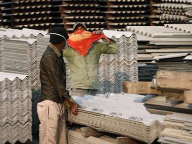 In this Nov. 23, 2013 photo, a worker covers his face with a handkerchief as he sees people photographing him and his coworker handling asbestos sheets at the Ramco Industries Ltd. factory in Bhojpur district of Bihar. AP