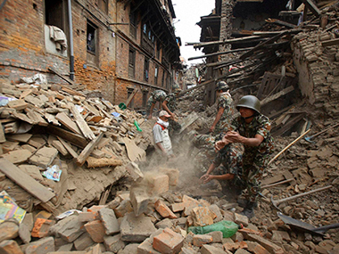 Rescue workers remove debris as they search for victims of earthquake in Bhaktapur near Kathmandu, Nepal. PTI