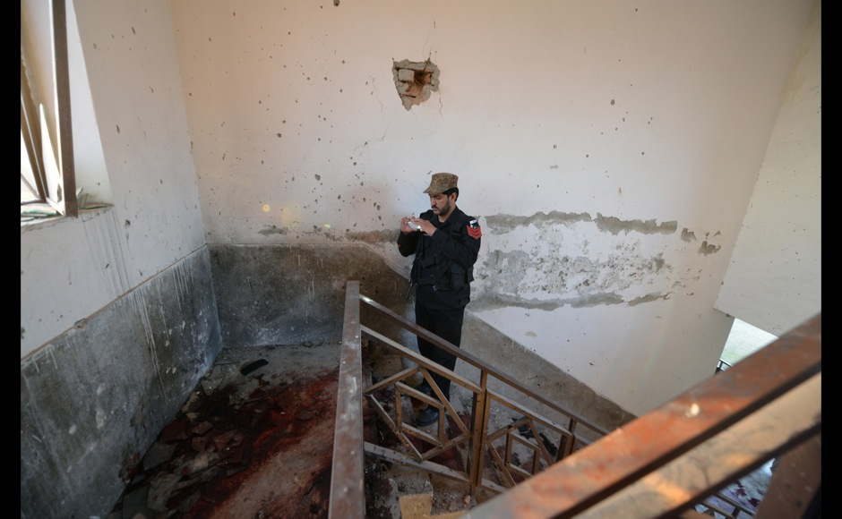 A Pakistani policeman takes photos of stairs splattered with blood, where Taliban militants were killed, at Bacha Khan university following an attack in Charsadda, about 50 kilometres from Peshawar, on20 January, 2016. At least 21 people died in a Taliban assault on a university in Pakistan, where witnesses reported two large explosions as security forces moved in under dense fog to halt the bloodshed. AFP PHOTO