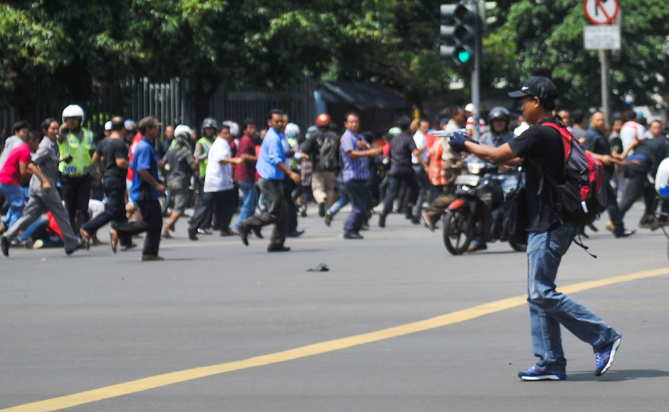 In this photo released by China's Xinhua news agency, an unidentified man with a gun walks in the street as people run in the background on Thamrin street near Sarinah shopping mall in Jakarta, Indonesia. Suicide bombers exploded themselves in downtown Jakarta while gunmen attacked a police post nearby. AP