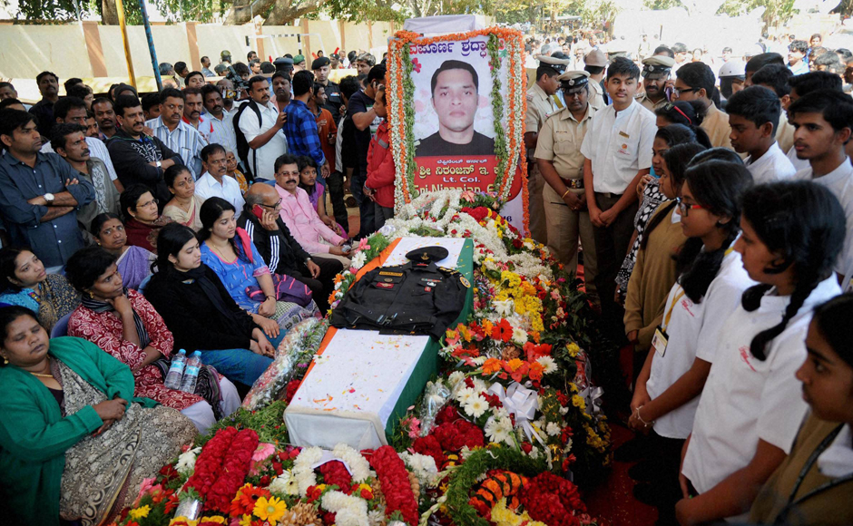 People gather near the mortal remains of Lt Col Niranjan Kumar at his home in Bengaluru on Monday. Kumar, a Lieutenant Colonel with the National Security Guard's Bomb Disposal Squad, lost his life while defusing a grenade during the Pathankot terror attack on Sunday. PTI