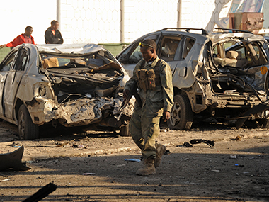 A Somali soldier walks past the attack scene. AFP
