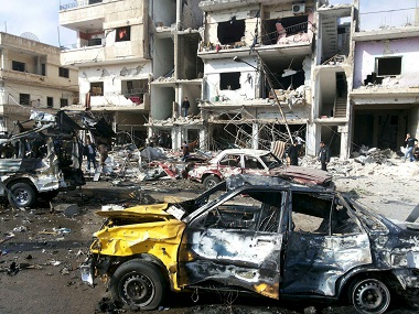 People inspect the site of a two bomb blasts in Homs, Syria, on Sunday. Reuters/SANA