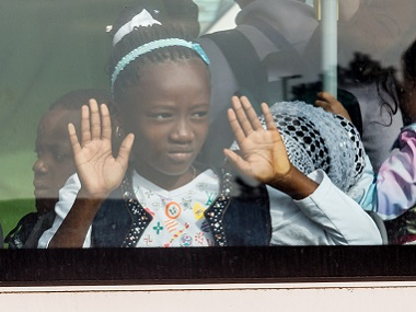 A young girl looks out of the window of a bus after being evacuated from Brussels airport. AP