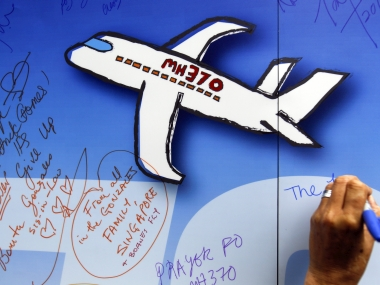 A Malaysian writes well wishes on a wall of hope during a remembrance event for the ill fated Malaysia Airlines Flight 370 in Kuala Lumpur. AP