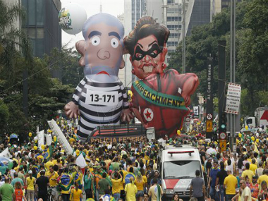 "Demonstrators parade large inflatable dolls depicting Brazil's former President Luiz Inacio Lula da Silva in prison garb and current President Dilma Rousseff dressed as a thief, with a presidential sash that reads ""Impeachment,"" in Sao Paulo, Brazil, Sunday, March 13, 2016. AP"