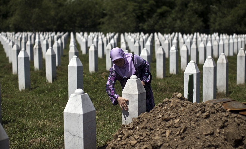 A file image of a woman touching the tombstone of a relative at the Potocari, memorial complex near Srebrenica. AP