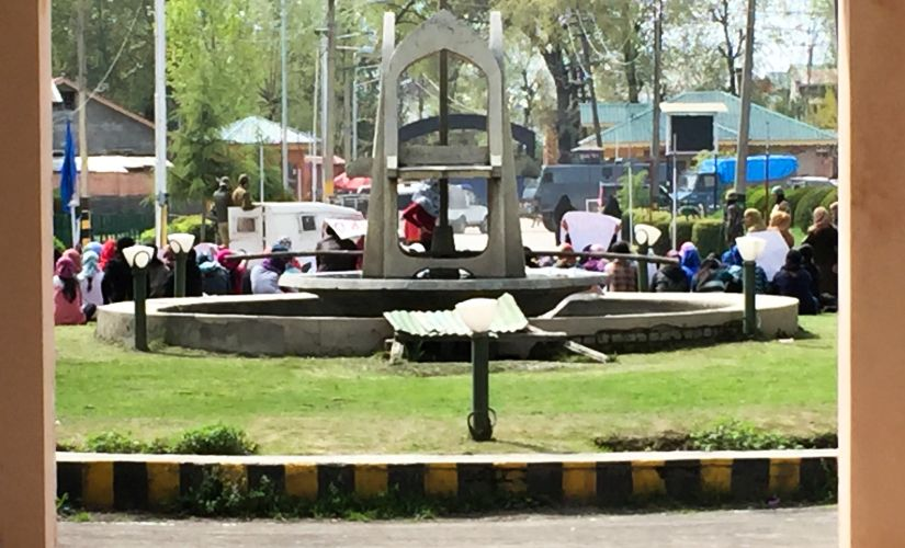 A group of girl students during a sit-in on the base of a fountain, CRPF vehicles can be seen clocking the main road from the campus. Sameer Yasir