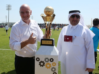 FIFA President Gianni Infantino (L) poses for a picture with the workers football cup trophy during a match ahead of a press conference in the Qatari capital Doha. AFP