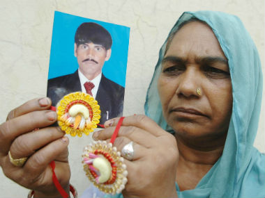 A family member holds up Kirpal Singh's photograph. AFP