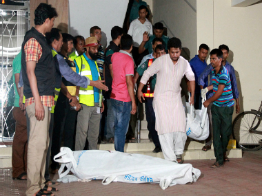 The bodies of two gay rights activists who were hacked to death are brought down from an apartment in Dhaka on. Getty Images