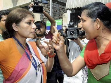 BJP candidate Rupa Ganguly arguing with an activist of a rival political party at a polling booth in Howrah on Monday. PTI