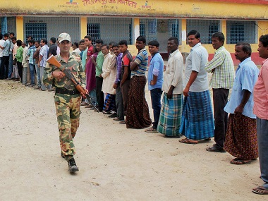 A security official keeps vigil as voters wait to cast their votes at a polling station in South Dinajpur on Sunday. PTI