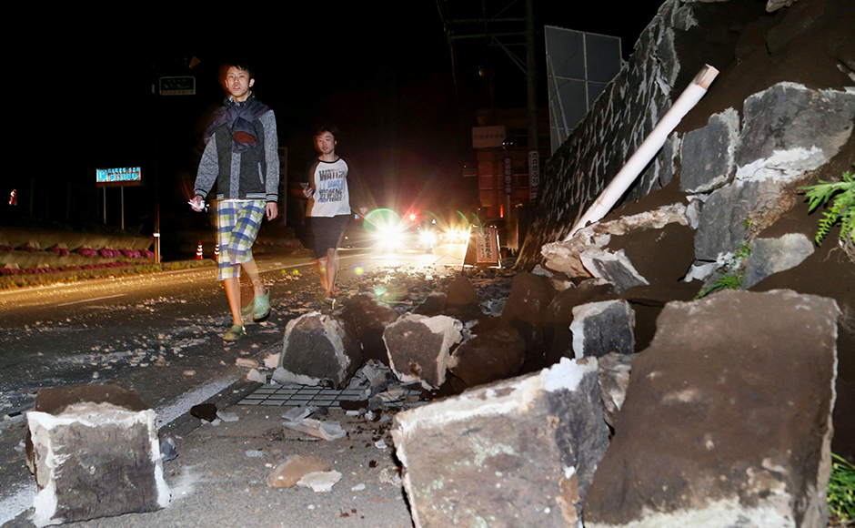 People walk past fallen walls after an earthquake of 6.4 magnitude hit the town of Mashiki, in Kumamoto, southern Japan on Thursday. Police said people weretrapped underneath the rubble. AP