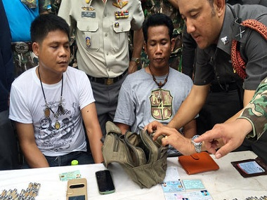 A police officer examines the belongings of two men arrested for removing tiger skins and products from the Tiger Temple. AP.