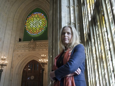 """Artist Mary Branson poses in front of her art work """"New Dawn"""". UK Parliament via AP"""