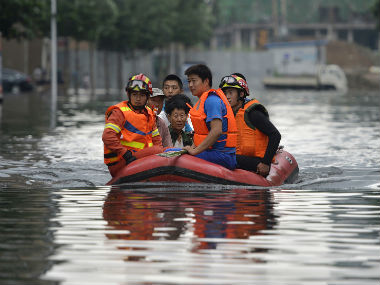 Rescuers use rafts to ferry people from flood hit areas. AP