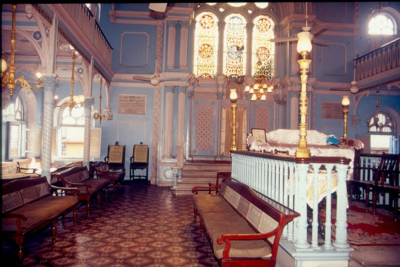 The minton tiled flooring and the 'tebah' (akin to a pulpit) are seen in the foreground, while large stained glass windows are seen above the Holy Ark of the Keneseth Eliyahoo synagogue (1884) in Fort , Mumbai. Image courtesy Jamshed Lentin
