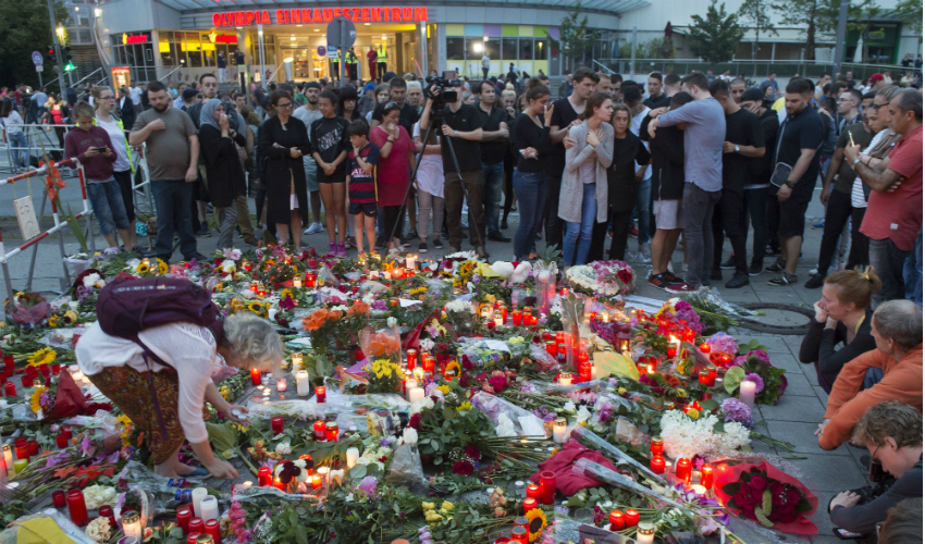 Munich new2_People gather to mourn with flower tributes near to the Olympia shopping center where a shooting took place leaving nine people dead the day before in Munich on Saturday. AP