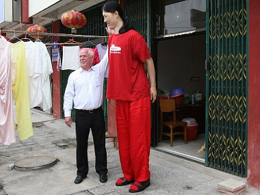 Georg Wessels (L), a German maker of outsize shoes, chats with Yao Defen, believed to be the tallest woman in Asia at 2.36 m (7ft 8in). Reuters