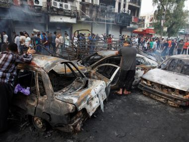 People inspect the site of a suicide car bomb in Baghdad. Reuters