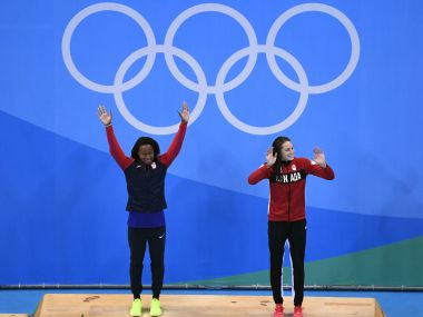 Gold medalist Simone Manuel and Penny Oleksiak celebrate on the podium. Getty