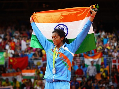 PV Sindhu of India celebrates with the Indian flag after clinching silver. Getty Images