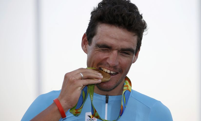 Greg Van Avermaet bites the gold medal. Reuters