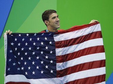 United States' Michael Phelps walks with his national flag during the medal tally ceremony for the men's 4 x 100-meter medley relay. AP