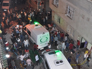 "People carry dead bodies into ambulances after an explosion in Gaziantep, southeastern Turkey, early Sunday, Aug. 21, 2016. A bomb attack targeting an outdoor wedding party in southeastern Turkey killed several people and wounded dozens. Deputy Prime Minister Mehmet Simsek said the ""barbaric"" attack in Gaziantep, near the border with Syria, on Saturday appeared to be a suicide bombing. (DHA via AP)"