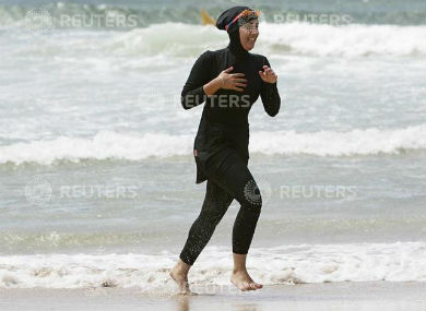 "Twenty-year-old trainee volunteer surf life saver Mecca Laalaa runs along North Cronulla Beach in Sydney during her Bronze medallion competency test January 13, 2007. Specifically designed for Muslim women, Laalaa's body-covering swimming costume has been named the ""burkini"" by its Sydney based designer Aheda Zanetti. REUTERS"