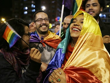 People celebrate in a park as they listen to the announcement from Havana, Cuba, that delegates of Colombia's government and leaders of the Revolutionary Armed Forces of Colombia reached a peace accord to end their half-century civil war. AP
