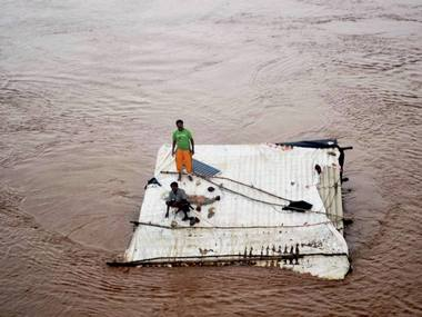 People marooned on the top of a submerged house in flood-hit in Nashik's neighbouring town, Valsad town on Tuesday after heavy rains. PTI