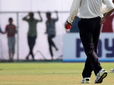 An umpire holds a pink ball as he walks during a tea break in the Duleep Trophy. AFP