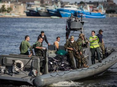 An Egyptian coast guard dinghy brings bodies from a Europe-bound boat that capsized off Egypt's Mediterranean coast. AP