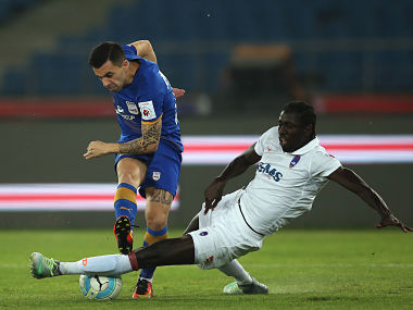 Matias Defederico of Mumbai City FC attempts a shot at goal as Baye Ibrhima Niasse of Delhi Dynamos FC makes the tackle. ISL