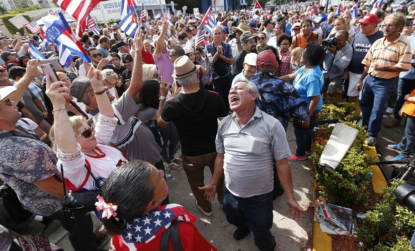 Members of the Cuban community react to the death of Fidel Castro, Saturday, Nov. 26, 2016, in the Little Havana area in Miami. Castro, who led a rebel army to improbable victory in Cuba, embraced Soviet-style communism and defied the power of 10 U.S. presidents during his half century rule, died at age 90. (AP Photo/Wilfredo Lee)