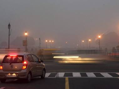 Vehicles ply on smog covered Rajpath in New Delhi on Saturday. PTI