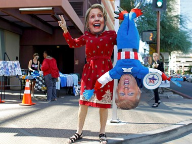 A man wears a mask depicting Democratic US presidential candidate Hillary Clinton while holding a doll depicting Republican presidential nominee Donald Trump. Reuters