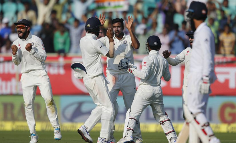 Ravichandran Ashwin celebrates with teammates the dismissal of Joe Root on the second day of Vizag Test. AP