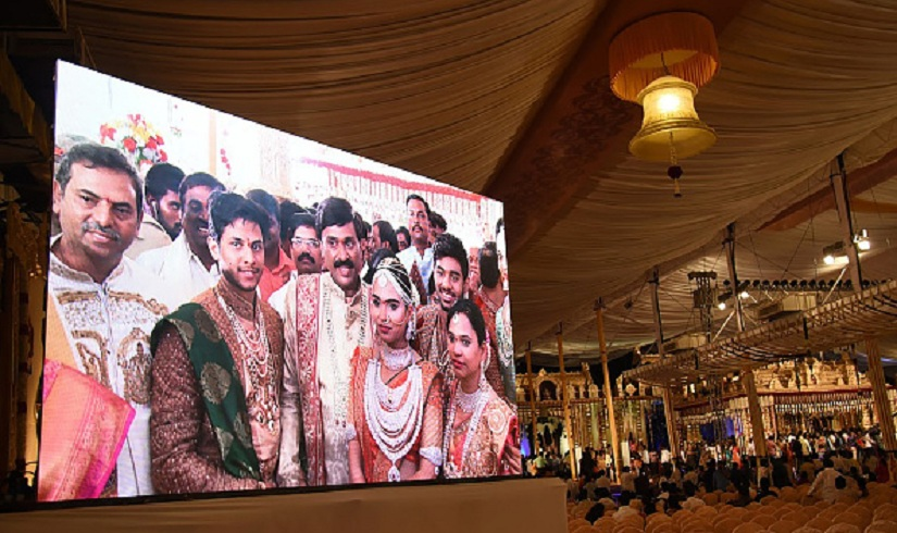 Indian mining tycoon, Gali Janardhan Reddy, (C) is seen on a big screen as he poses with his daughter Bramhani (2R) and son-in-law, Rajeev Reddy (2L) during their wedding at the Bangalore Palace Grounds in Bangalore. A controversial Indian mining tycoon has taken over a royal palace and flown in Brazilian dancers at a reported cost of 75 million dollars to celebrate his daughter's wedding, as the country reels from a cash crisis. / AFP / STRINGER (Photo credit should read STRINGER/AFP/Getty Images)