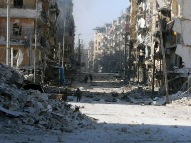 Syrians walk over rubble of damaged buildings. Reuters