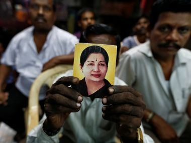 A supporter Jayalalithaa holds her photo. Reuters